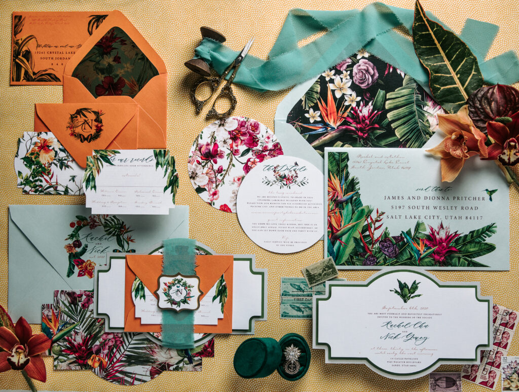 A flat lay of hand painted blue and orange and tropical theme invitation