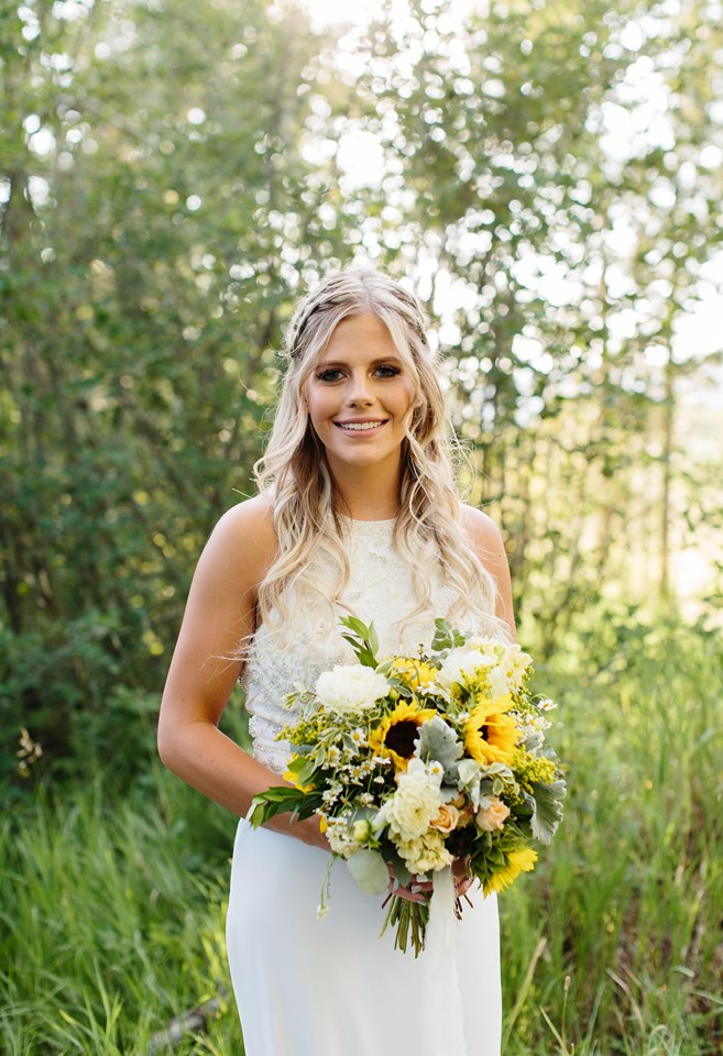 Summer bride with sunflower bouquet in the mountain