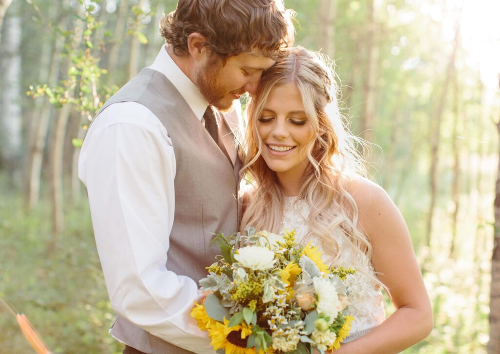 A newlywed couple in the mountains for an elopement with glamour makeup and a yellow bouqet