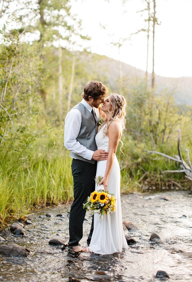 In love couple barefoot in a mountain river with a sunflower bouquet