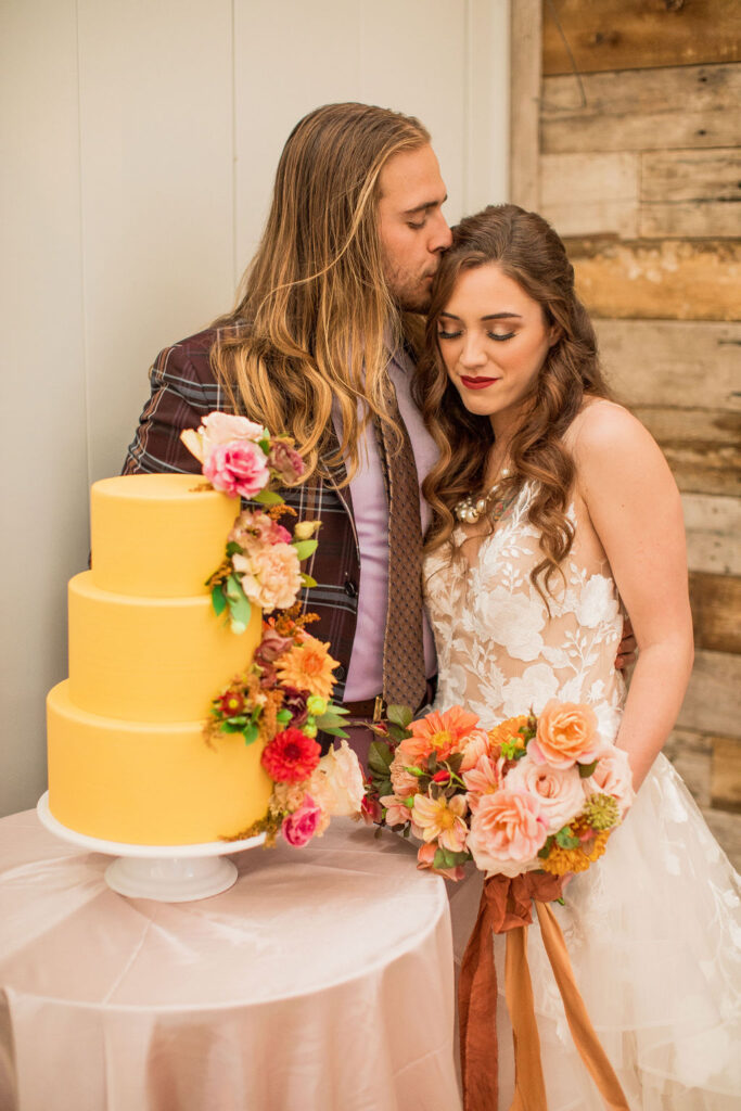 Yellow wedding cake with florals with professional hair and makeup on bride and groom