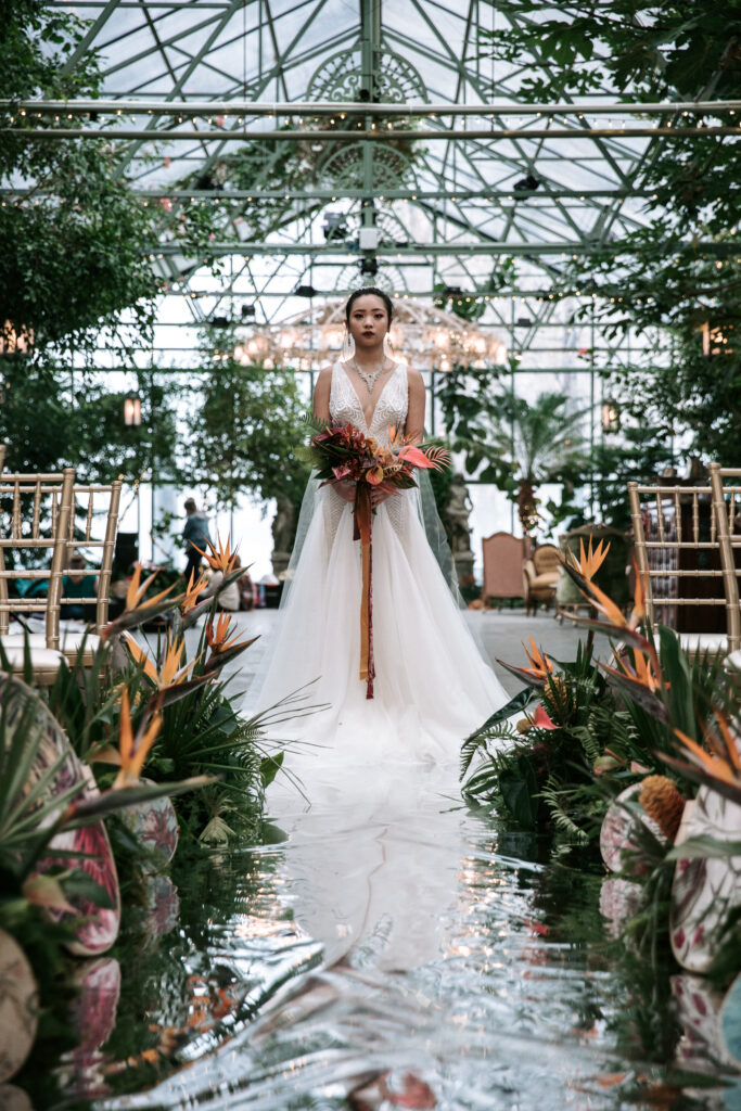 An asian bride in a designer wedding dress about to walk down a shimmering water aisle based off the movie Crazy Rich Asians