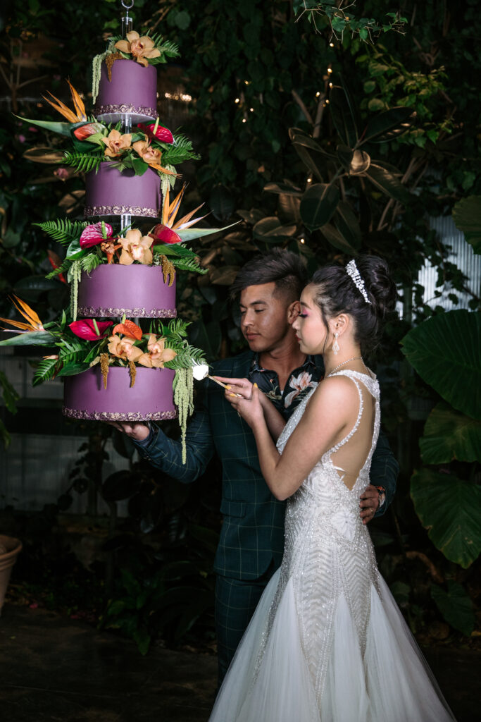 A purple wedding cake with tropical flowers with an asian bride and groom about to cut the cake