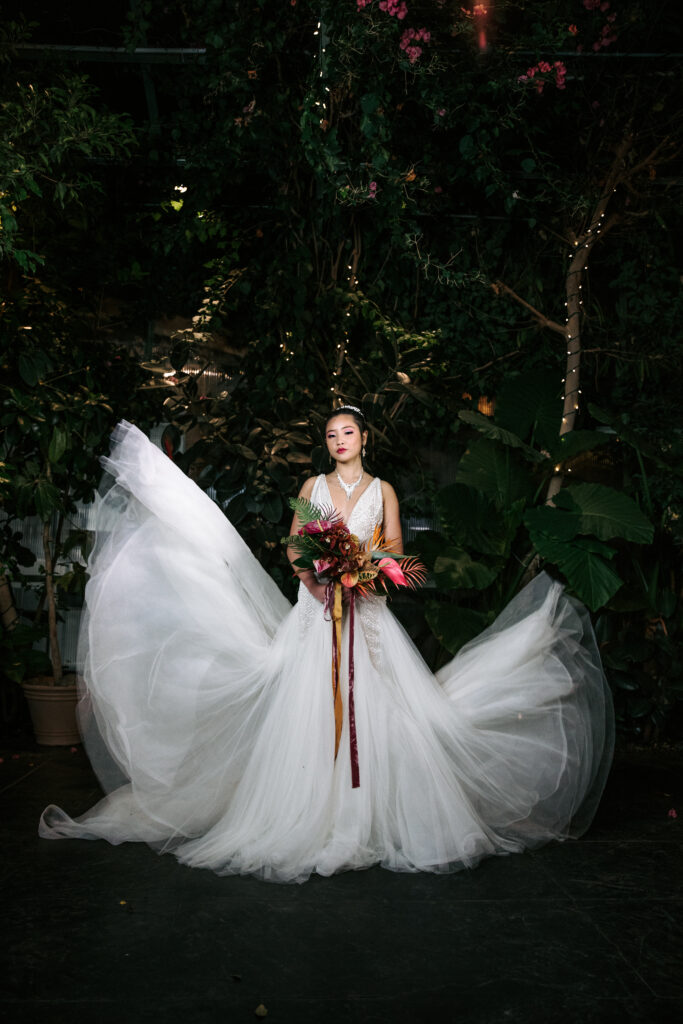 Asian bride in imported wedding dress with a tropical bouquet